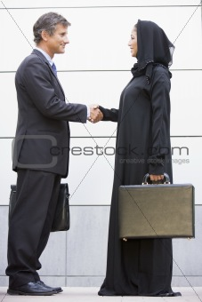 A caucasian businessman and Middle Eastern woman shaking hands