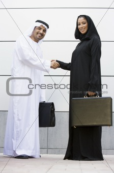 A Middle Eastern businessman and woman shaking hands