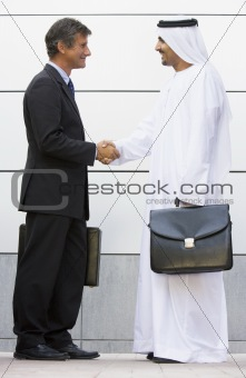 A Middle Eastern and a caucasian businessman shaking hands