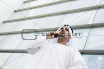 A Middle Eastern businessman talking on the phone outside an off