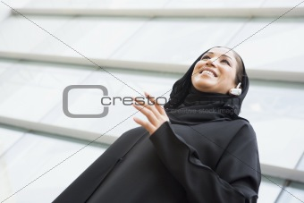 A Middle Eastern businesswoman standing outside an office block