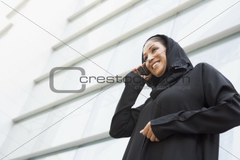 A Middle Eastern businesswoman talking on the phone outside an o