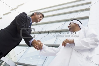 A Middle Eastern businessman and Caucasian man shaking hands out