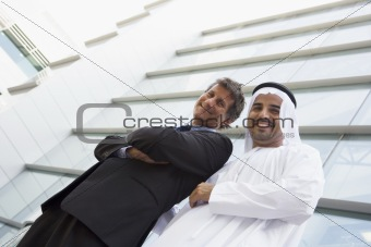 A Middle Eastern businessman and Caucasian man standing outside