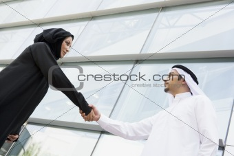 A Middle Eastern businessman and woman shaking hands outside an