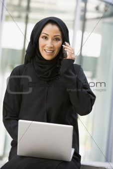 A Middle Eastern business woman sitting with a laptop