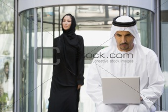 A Middle Eastern businessman sitting with a laptop