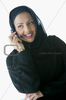 A Middle Eastern businesswoman talking with headphones