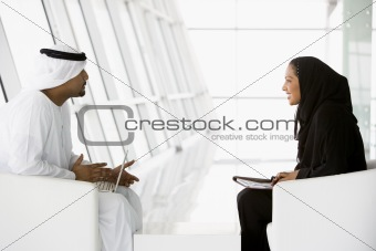 A Middle Eastern man and woman talking at a business meeting