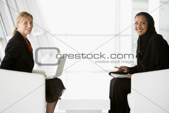 A Middle Eastern and caucasian woman talking at a business meeti