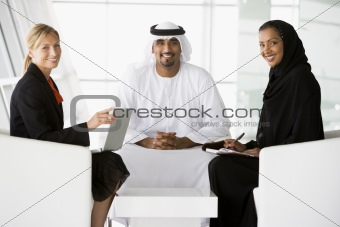 A Middle Eastern man and woman and a caucasian woman talking at
