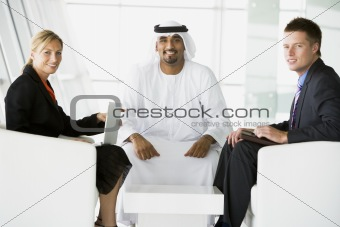 A Middle Eastern man and a caucasian man and woman talking at a
