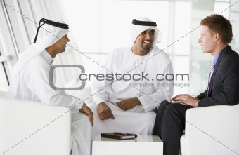 Two Middle Eastern men and a caucasian man talking at a business