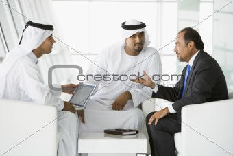 Three Middle Eastern men talking at a business meeting