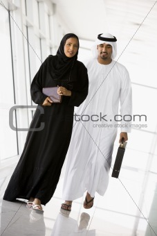 A Middle Eastern businessman and woman walking in a corridor
