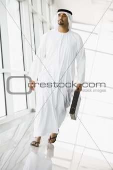 A Middle Eastern businessman walking in a corridor
