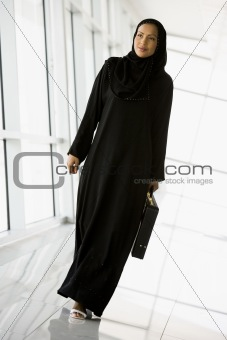 A Middle Eastern businesswoman walking in a corridor