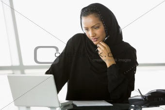 A Middle Eastern businesswoman using a laptop