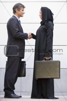 A Middle Eastern businesswoman shaking hands with a Caucasian bu