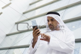 A Middle Eastern businessman using a PDA