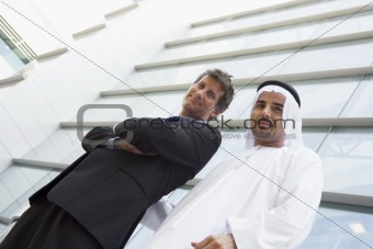 A Middle Eastern businessman and a Caucasian businessman smiling