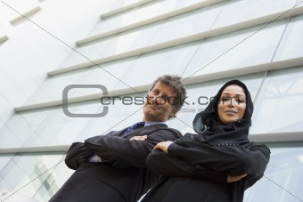A Middle Eastern businesswoman and a Caucasian businessman smili