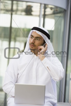 A Middle Eastern businessman using a mobile phone and laptop