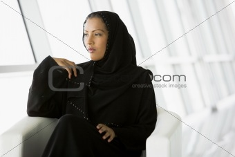 A Middle Eastern businesswoman gazing out of a window