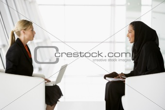 A Middle Eastern businesswoman talking to a Caucasian businesswo