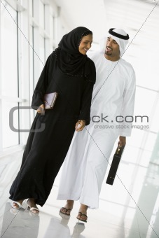 A Middle Eastern businessman and businesswoman walking down a co