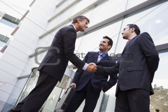 Business people shaking hands outside office