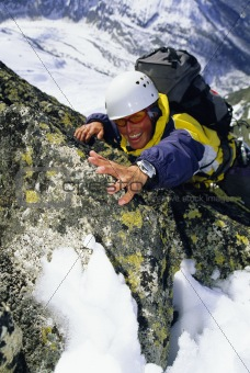 Mountaineer climbing snowy rock face