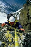 Mountaineer scaling snowy rock face