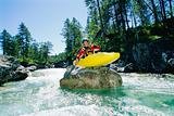 Kayaker perched on boulder in river