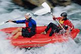 Two people paddling inflatable boat down rapids