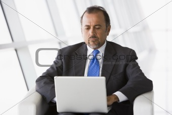 Businessman working on laptop in lobby