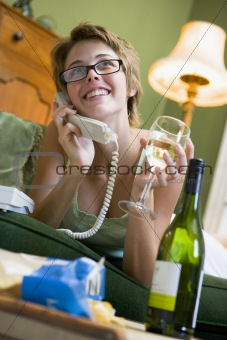 A young woman in her pyjamas on the phone and drinking wine