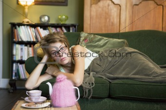 A young woman lying on her couch