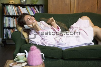 A young woman lying on her couch talking on the phone and eating