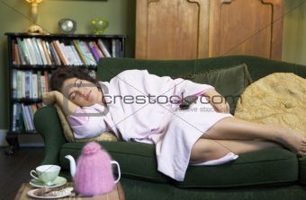A young woman lying on her couch having a nap