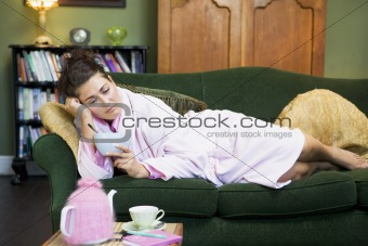 A young woman lying on her couch eating cereal