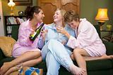 Three young women drinking wine together in their pyjamas