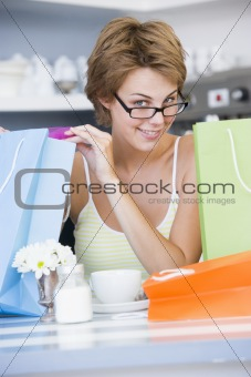 A young woman sitting in a cafe with shoping bags