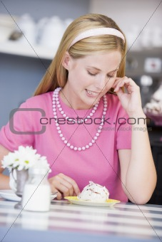 A young woman sitting in a cafe eating a sweet treat