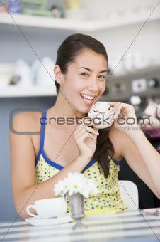 A young woman eating cake in a cafe