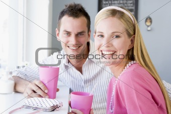 A young couple drinking milkshakes in a cafe