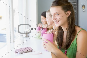 A young woman drinking a milkshake in a cafe