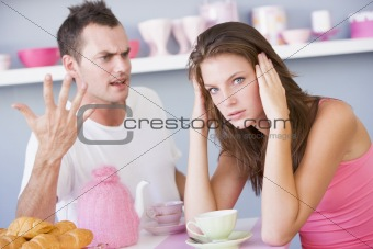A young couple arguing at the breakfast table