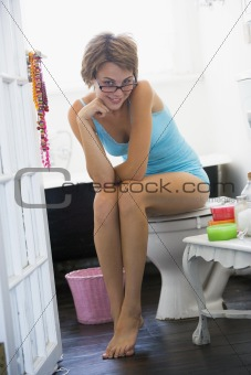 A young woman sitting in the bathroom