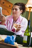 A young woman in her pyjamas drinking wine and frowning at her t